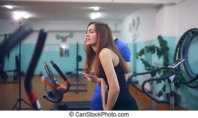 Girl on the exercise bike and a man with a clipboard in gym...