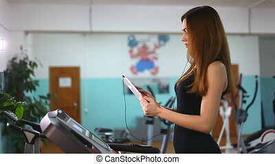 girl in gym and tablet - girl with the tablet on treadmill...