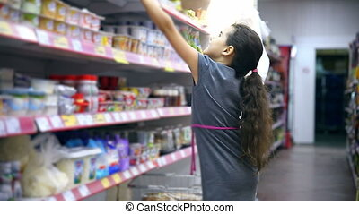 girl teen in supermarket to buy dairy food yogurt