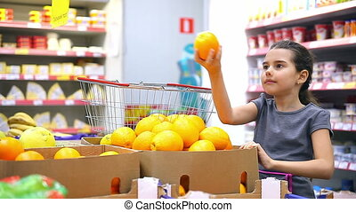 girl teen with in supermarket to buy fruit orange - girl...