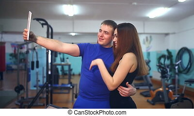 man and woman in gym doing self on the tablet athletes...