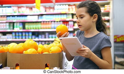 girl teen with tablet in supermarket to buy orange - girl...