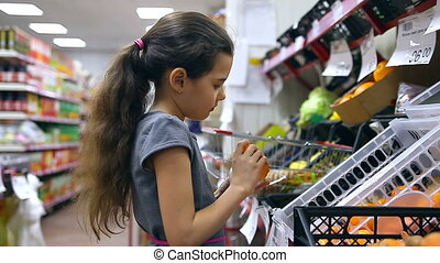 girl teen in supermarket to buy persimmon fruit food
