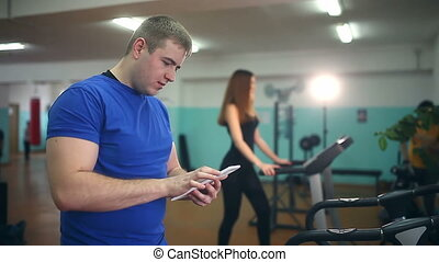man coach in gym girl with the tablet on the treadmill fitness, healthy lifestyle, sport