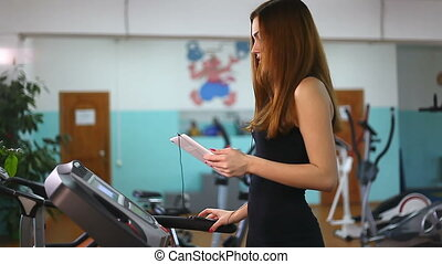girl with the tablet on the treadmill exercise at the gym,...