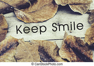 word KEEP SMILE surrounded by dry leaves.old wooden background and retro look theme