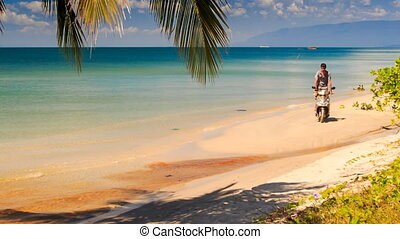 Guy Standing on Motorbike Drives to Palm on Beach - guy...