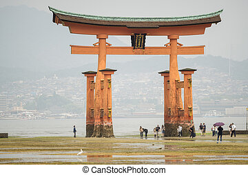 Miyajima, Floating Torii gate in Japan with blurred tourists...