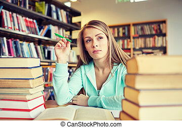 bored student or young woman with books in library - people,...