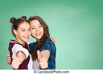 happy teenage student girls showing thumbs up - people,...