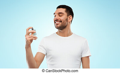 smiling man with male perfume over gray background -...