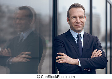 Confident male businessman leaning on window