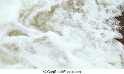 Pebbles and surf at sea - On pebble beach foam sea surf