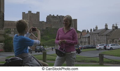 Take a Picture! - Son taking a photograph of his mother with...