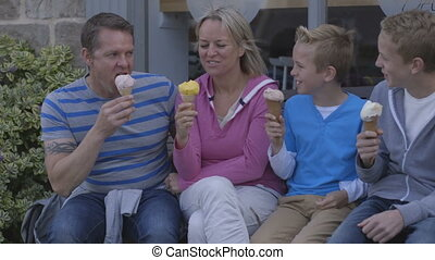 Enjoying Ice-cream - Family of four enjoying ice-cream...