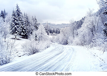 Snow-covered road winding among forest - Snow-covered road...