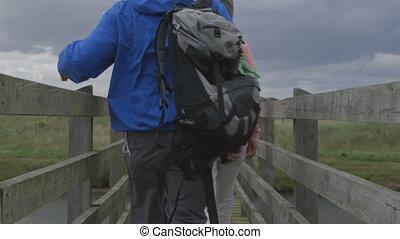 Countryside Walks - Family of four walking across a bridge...