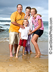 Happy family at the beach - A happy family of mom, dad,...