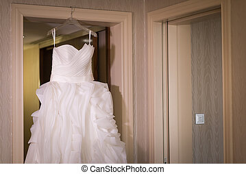 White wedding gown hanging at doorway.