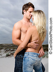 Topless couple embrace on the beach - A topless man with his...