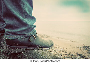 Man in jeans and elegant shoes standing on fallen tree on...