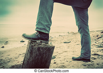 Man in jeans and elegant shoes leaning against trunk tree on...