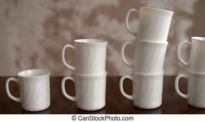 Mugs placed on a table in a pyramid - White tea mugs are...