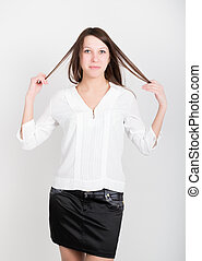 Beautiful slim girl in a short black skirt and white blouse, holding his hair