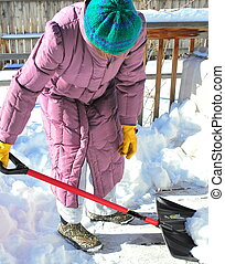 Winter snow out doors - Mature female shoveling winter snow...