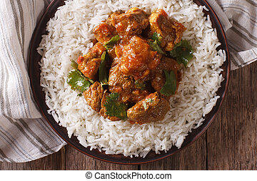 beef madras with basmati rice close-up on a plate....