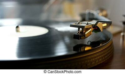 Turntable with spinning vinyl records and stylus going down.