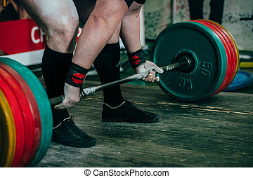 male athlete of powerlifter preparing for deadlift of...