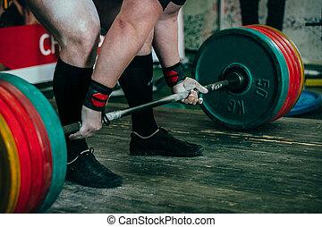 male athlete of powerlifter preparing for deadlift of...