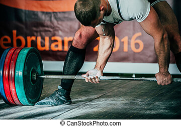 lift heavy weights. male athlete deadlift in competition
