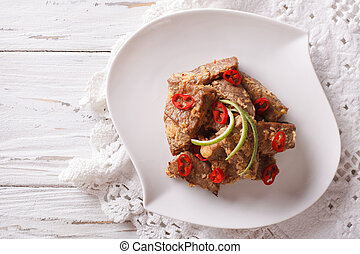 Rendang beef with spices close-up on a plate. Horizontal top...