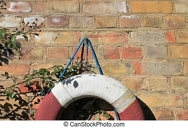 Life Buoy preserver attached to a red brick Wall with Plenty...
