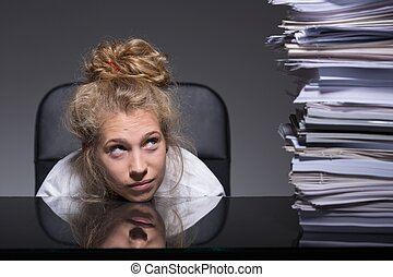 Young woman and paperwork - Young woman is stressed about...
