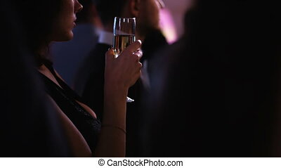 Medium shot footage of girl worn in a fancy night dress is keeping a glass of champagne at concert hall.