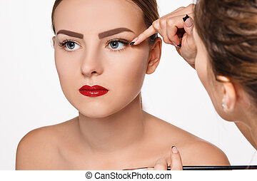 Beautiful female eyes with make-up and brush on white....