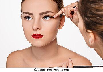 Beautiful female eyes with make-up and brush on white....