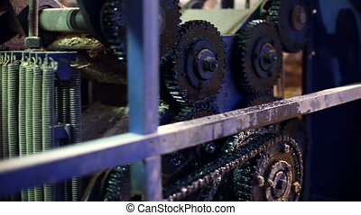Sawmill. View on gears in working machine, close-up