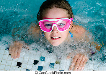 Cute happy girl in pink goggles mask in the swimming pool