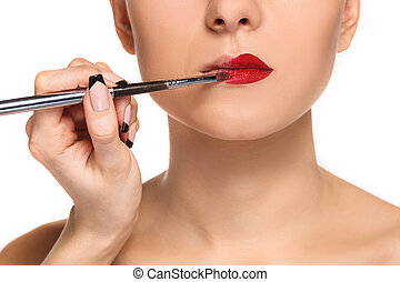 Beautiful female lips with make-up and brush on white Makeup...