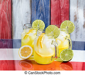 Glass mugs filled with cold lemonade on USA national colors...