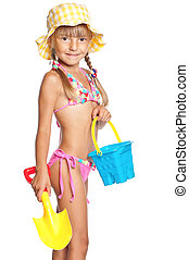 Happy little girl in swimsuit with bucket and spade isolated...