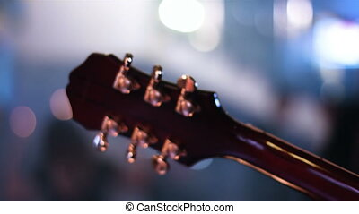 Detail footage of guitar headstock which is played by...