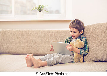 boy playing with digital tablet - Cute little boy playing...