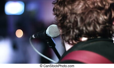 Close-up picture of singer sitting toward a microphone at...