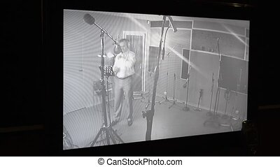 Man sing in studio in front of microphone Surveillance...