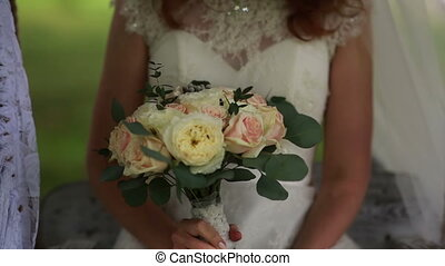 bride on a swing while holding a bouquet in hands - young...